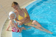 Mother and child sit at swimming pool Stock Photography