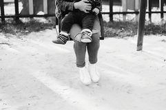 Mother and child sit on a swing and rest after a walk. In the park around only sand and wind Stock Photos