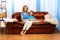 Mother and child sitting on couch at home Stock Photography