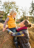 Mother and child sitting on haystack Stock Photo