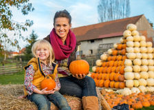 Mother and child sitting on haystack Royalty Free Stock Image