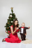 Mother and child are sitting at the new-year tree on white studi Royalty Free Stock Photos