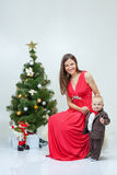 Mother and child are sitting at the new-year tree on white studi Stock Photo