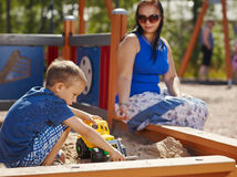 Mother and child. Mother and six year old boy child play together in sandbox Stock Photos