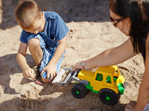 Mother and child. Mother and six year old boy child play together in sandbox Royalty Free Stock Photos
