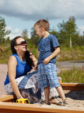 Mother and child. Mother and six year old boy child play together in sandbox Royalty Free Stock Photography