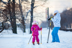 Mother and child on ski in city park Stock Photo