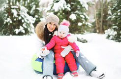 Mother and child on the sled having fun in winter Stock Image