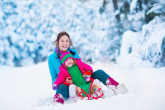 Mother and child sledding in a snowy park. Young mother and little girl enjoying sleigh ride. Child sledding. Toddler kid riding sledge. Children play outdoors Stock Photo