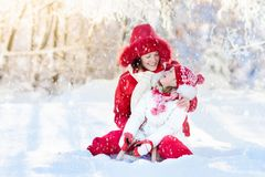 Mother and child sledding. Winter snow fun. Family on sleigh. Mother and baby on sleigh ride. Child and mom sledding. Toddler kid riding sledge. Children play Royalty Free Stock Images
