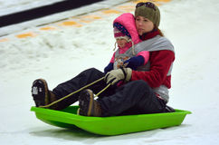 Mother with child on a snow slid slide downhill Stock Image