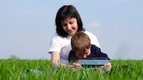 Mother and child spend time sitting on green grass and watching children`s movie on tablet computer. The movement of the slider. 4K stock video footage