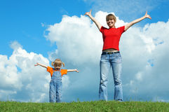 Mother and child stand on green grass Stock Photo