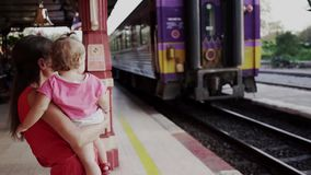 Mother and child are standing at the train station in Hua hin, Thailand, and waving to the departing train. Travel by stock video