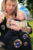 Mother with  child is started up with soap bubbles. Mother with  child on hands is started up with soap bubbles Royalty Free Stock Photos