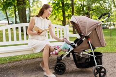 Mother with child in stroller reading book at park Royalty Free Stock Image