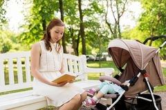 Mother with child in stroller reading book at park Stock Image