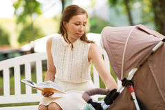 Mother with child in stroller reading book at park Stock Photography