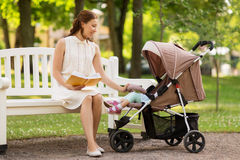 Mother with child in stroller reading book at park Royalty Free Stock Photos
