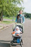Mother and child in the stroller walks in the park Stock Photography
