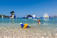 Mother and child swim and having fun in the water with inflatable slides in the background. stock photo