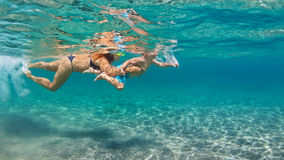 Mother with child swim underwater with fun in sea Royalty Free Stock Images