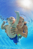 Mother with child swimming and diving underwater in pool Royalty Free Stock Image