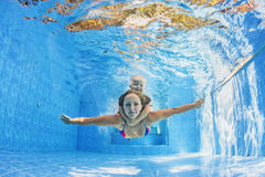 Mother with child swimming and diving underwater in pool Stock Photos