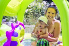 Mother and child swimming in the pool. Little kid learning and exercising in the water.  stock photo
