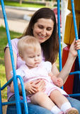 Mother and a child swinging in a playground. A mother and a child swinging in a playground Royalty Free Stock Photos