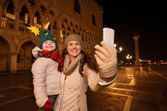 Mother with child taking selfie on Piazza San Marco in evening