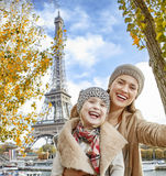 Mother and child taking selfie while sitting on parapet in Paris Stock Photo