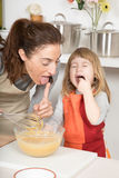 Mother and child tasting whipped cream at the same time Royalty Free Stock Photos