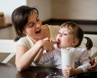 Mother and child tasting whipping cream Royalty Free Stock Photography