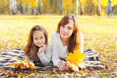 Mother and child together with yellow maple leafs in autumn Royalty Free Stock Photos