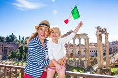 Mother and child tourists in front of Roman Forum rising flag. Roman Holiday. smiling modern mother and child tourists in the front of Roman Forum in Rome, Italy Stock Photos