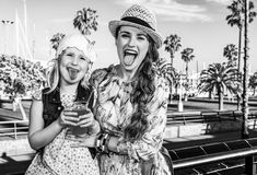 Mother and child tourists showing tongues after drinking bright. Summertime at colorful Barcelona. happy modern mother and child tourists on embankment in Stock Photos