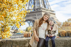 Mother and child tourists sitting on the parapet in Paris Royalty Free Stock Photography