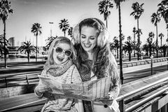 Mother and child travellers on embankment looking at map, Spain Royalty Free Stock Images