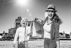 Mother and child travellers showing shoping bags. Roman Holiday. happy trendy mother and child travellers in the front of Palazzo Venezia in Rome, Italy showing stock photos