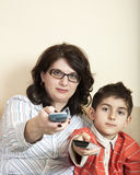 Mother and child with tv remote controls Royalty Free Stock Photo