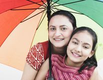 Mother and child and umbrella. Mother and daughter with a pretty rainbow umbrella stock image