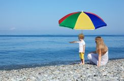 Mother with child under umbrella on pebble beach Royalty Free Stock Image