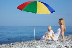Mother with child under umbrella on pebble beach Stock Image