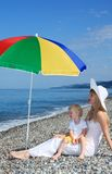Mother with child under umbrella on pebble beach royalty free stock photography