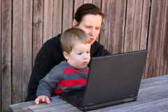 Mother and child using laptop outside. Mother and toddler using laptop together outside Royalty Free Stock Image
