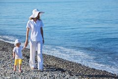 Mother with child walk on edge of sea Stock Photography