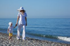 Mother with child walk on edge of sea Royalty Free Stock Photos