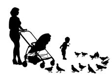 Mother with child on walk. Mother walks with the kids and a stroller for a walk. Mother and child feeding pigeons Royalty Free Stock Photo