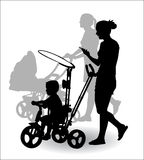 Mother with child on walk. Women with children ride in the stroller children for a walk Stock Images